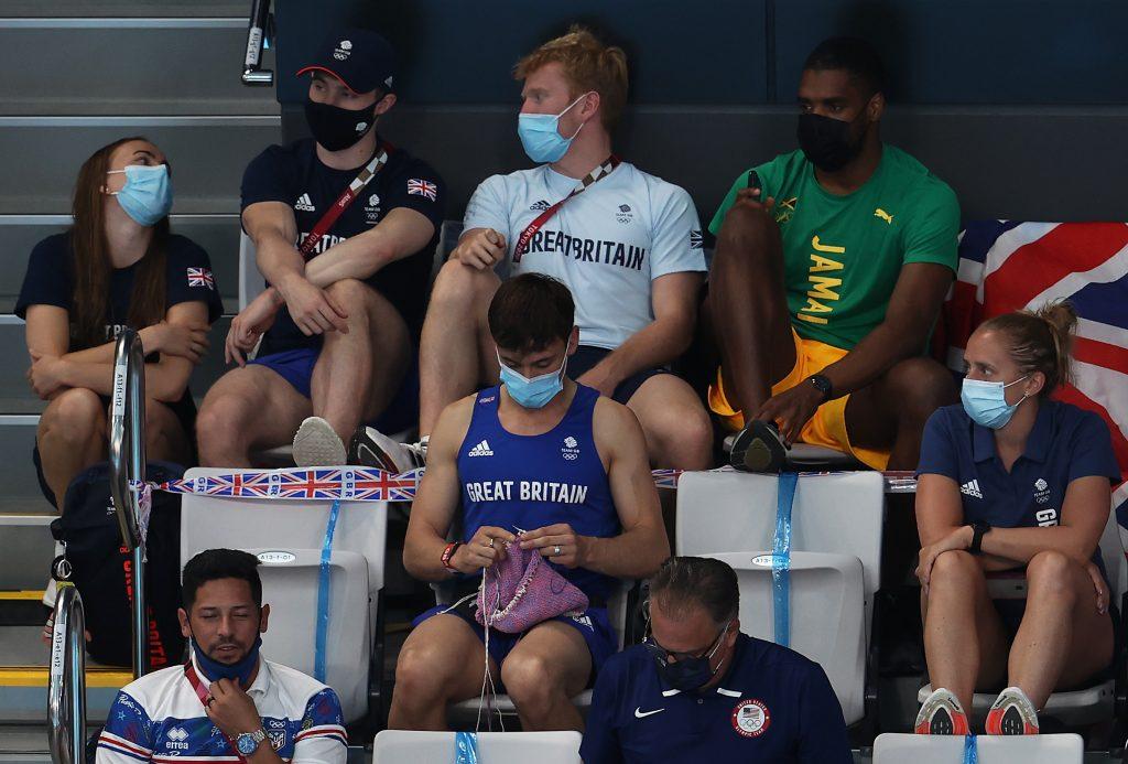 Le Britannique Tom Daley tricote en regardant la finale du tremplin féminin de 3 m lors de la neuvième journée des Jeux olympiques de Tokyo 2020.