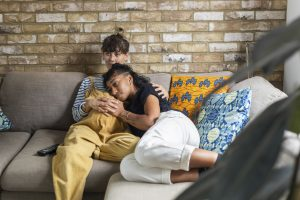 Deux femmes assises sur le canapé, l'une est enceinte et a des fibromes.