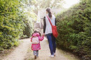 Enfant et mère se rendant à pied à l'école primaire