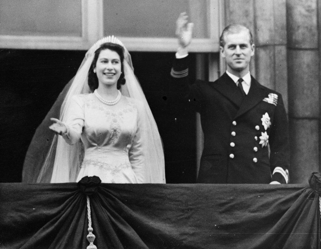La reine Elizabeth et le prince Philip, duc d'Édimbourg, saluent la foule depuis le balcon du palais de Buckingham.