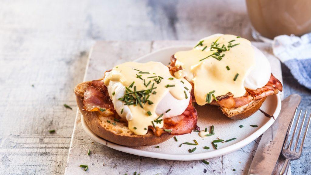 Œuf bénédictin traditionnel avec tranches de bacon sur toast, œuf poché et hollandaise - photo d'archive