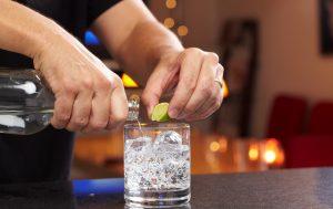 Homme préparant une boisson alcoolisée hypocalorique : vodka, citron vert et soda.