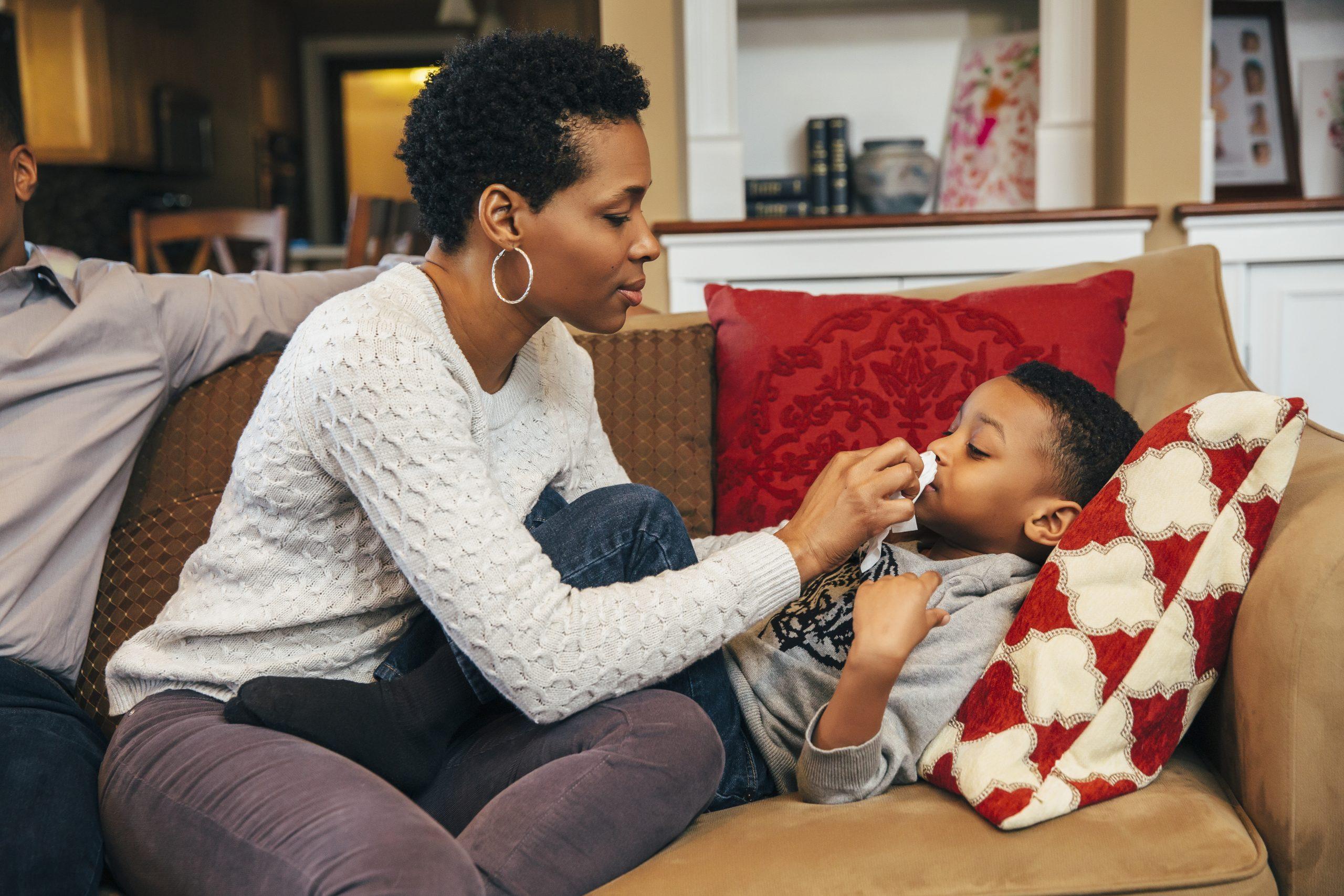 Une femme essuie le nez de son fils sur le canapé alors qu'il reste à la maison avec un rhume au lieu d'aller à l'école.