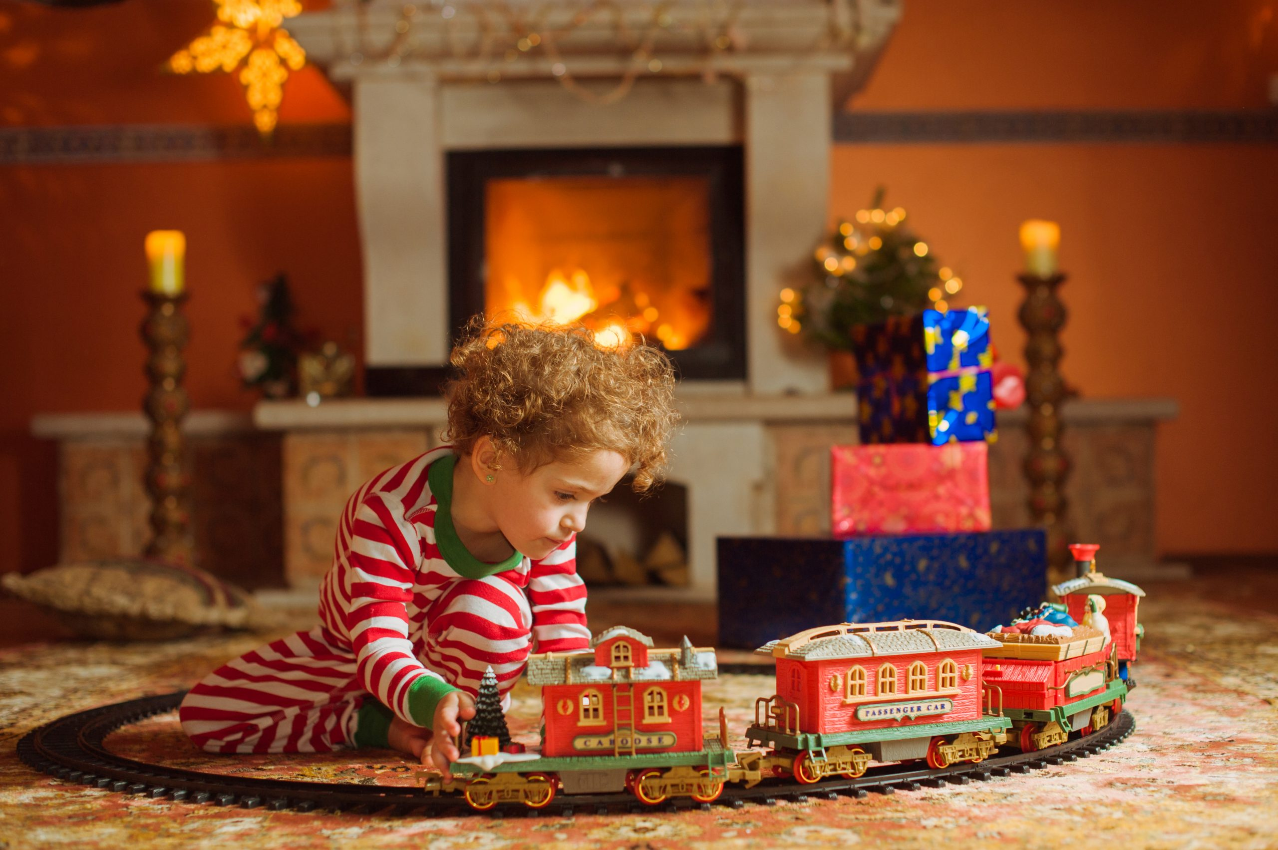 Fille, assise près de la cheminée parmi les décorations de Noël. Elle porte un pyjama rayé, elle a les cheveux bouclés. Fille jouant avec un train de Noël.