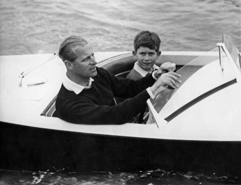 Le Prince Charles de Galles avec son père, le Prince Philip d'Edimbourg, à bord d'un bateau.