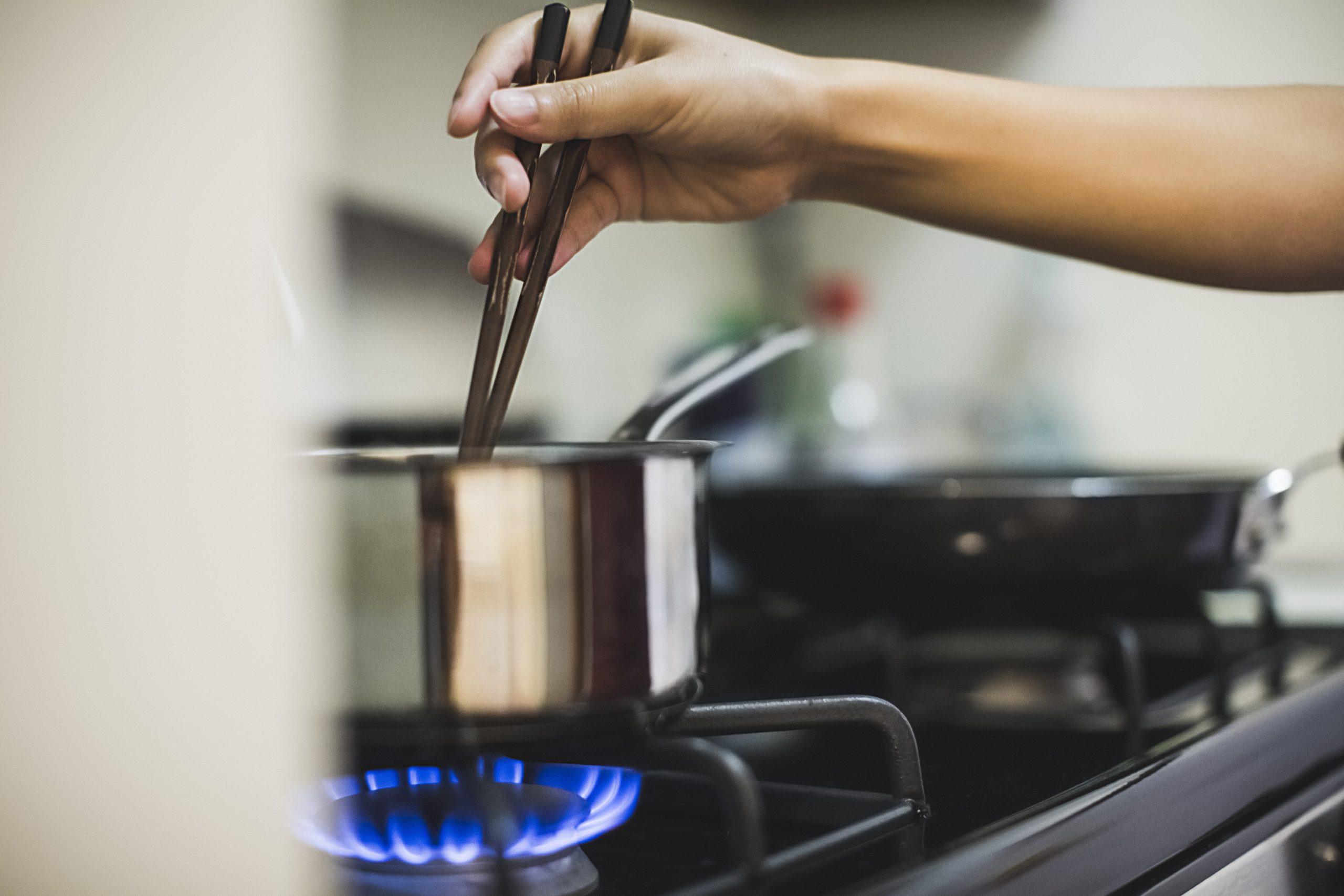 Une femme remue une casserole sur une plaque de gaz alors que les prix augmentent au Royaume-Uni.