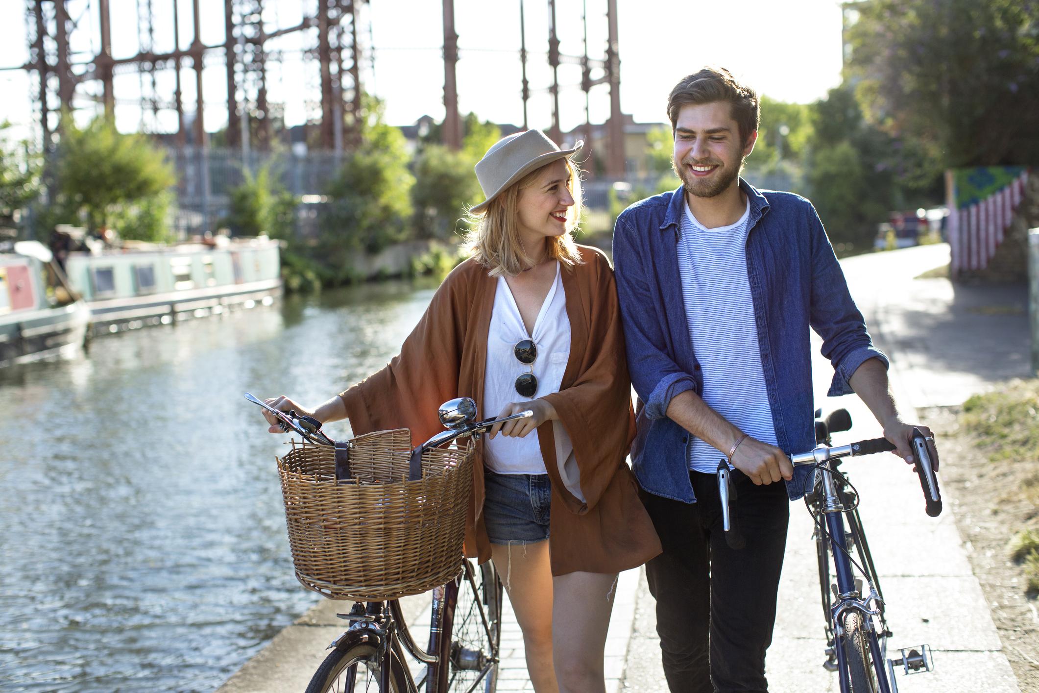 Deux personnes marchant ensemble avec des vélos le long d'un canal, une façon de soulager les gaz emprisonnés.