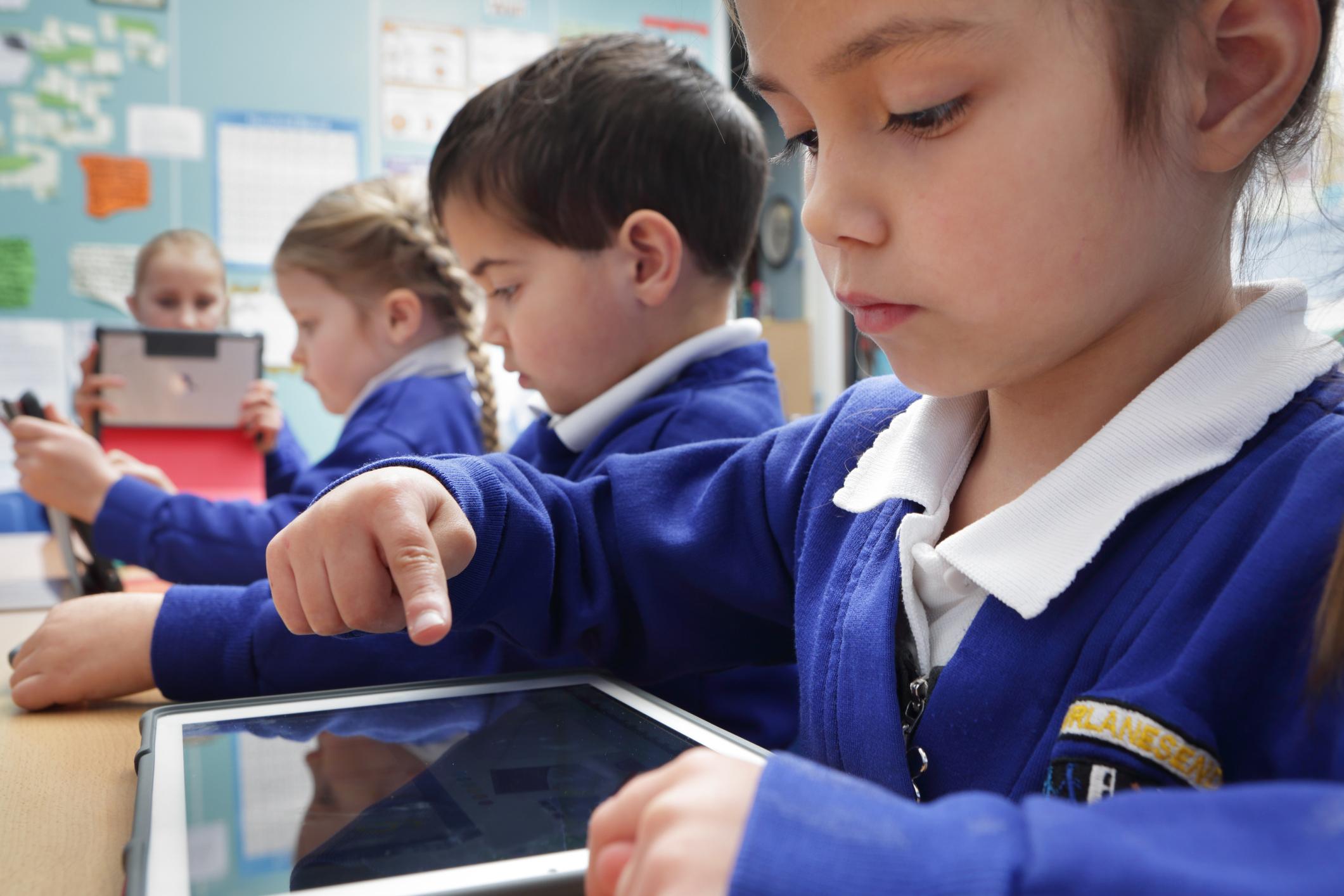 Des enfants à l'école travaillant sur des tablettes