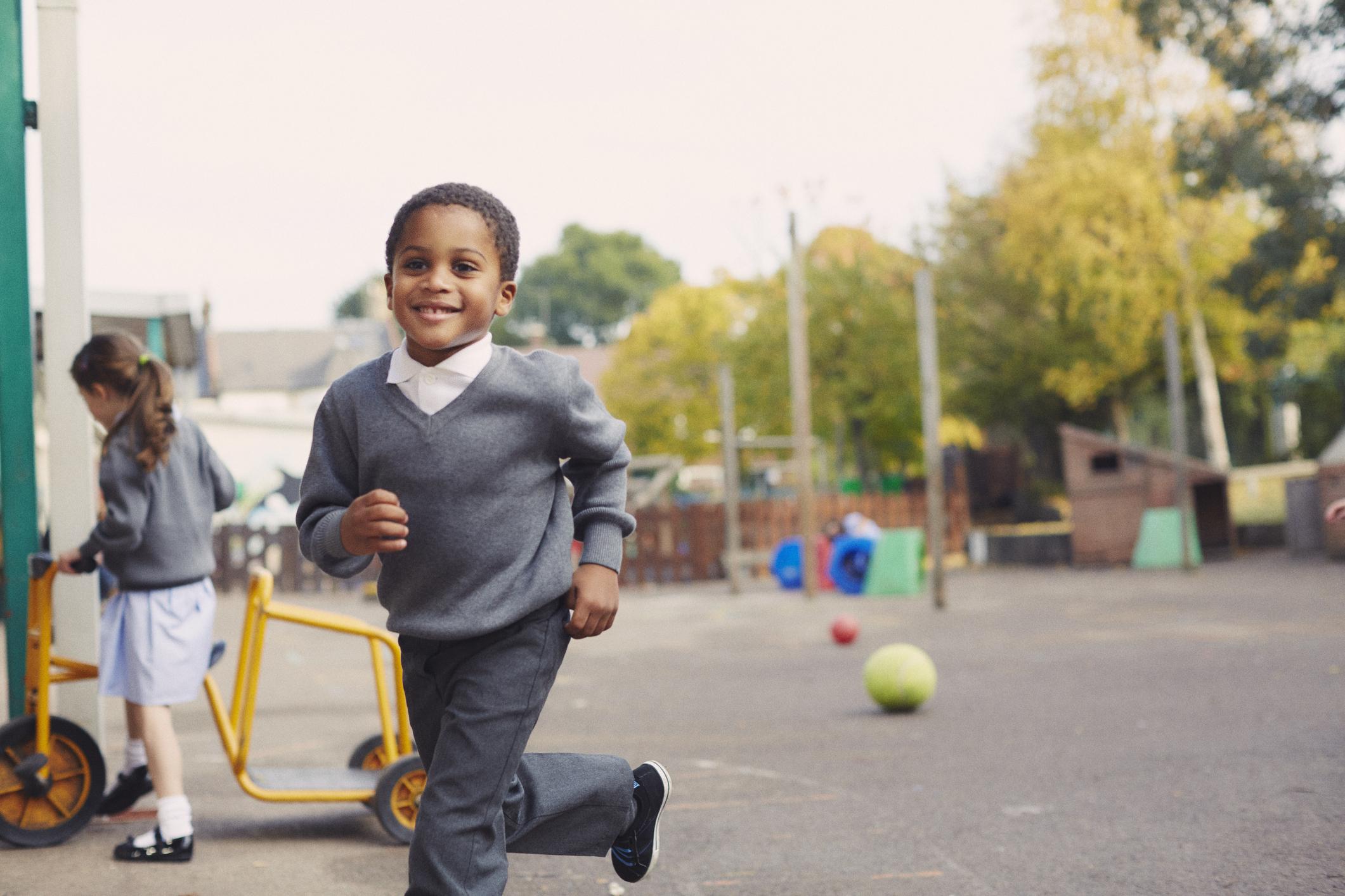 Garçon en uniforme scolaire courant dans la cour de l'école, quelque chose à demander lors de la visite d'une école primaire.