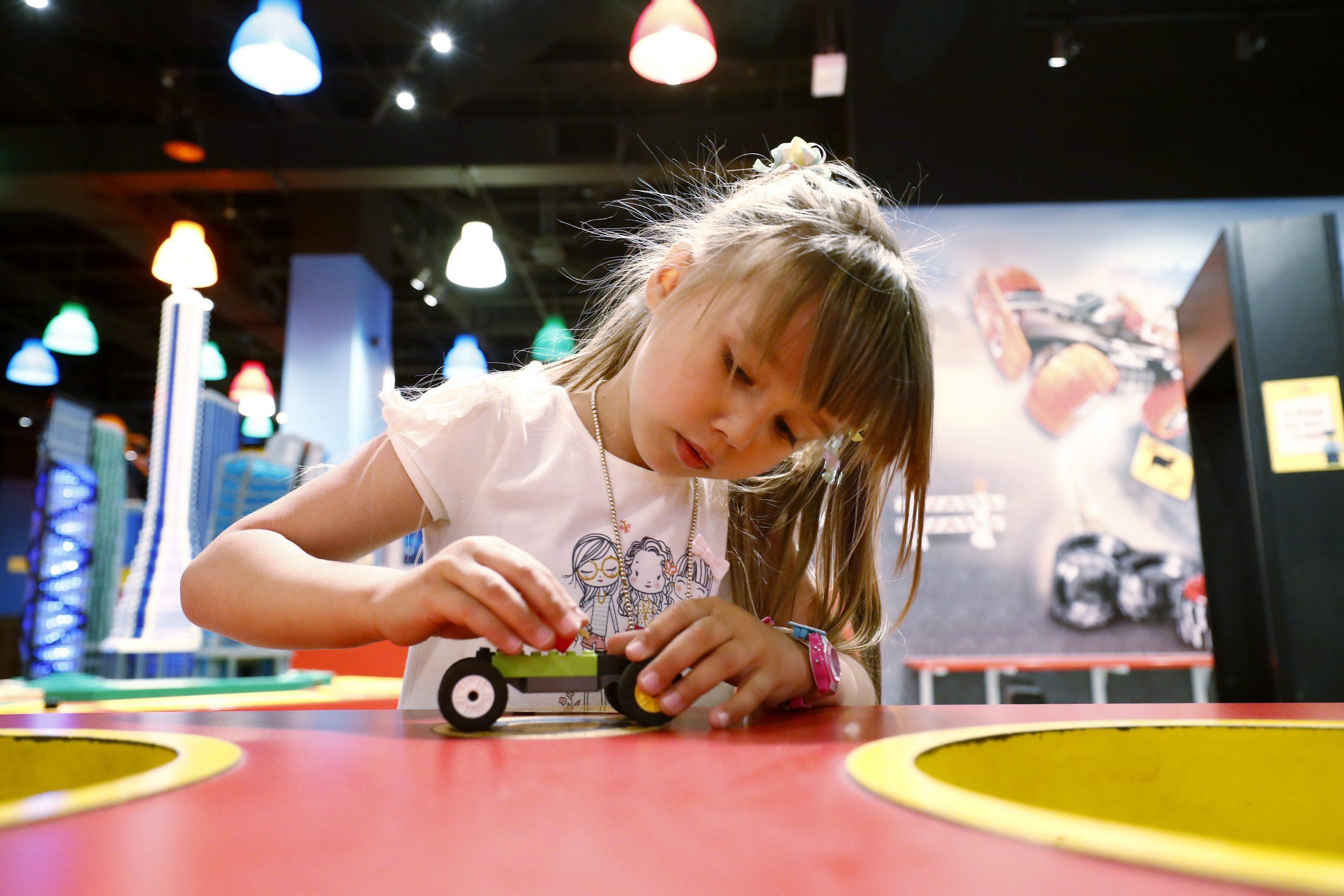 Fille jouant avec une voiture Lego